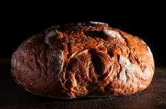 Rustikales Brot auf hölzernem Vorstand Stockfotos