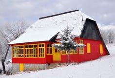 Rustikales farbiges Haus mit Schnee auf dem Dach Lizenzfreies Stockfoto