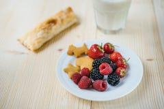 Rustikales gesundes Frühstück mit Blaubeere, Himbeere, Crackern, kleinem Laib und Milch in einem Glas auf einem Holztisch Stockbild