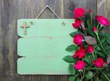 Rustikales grünes leeres Zeichen mit hölzerner Kreuz- und Blumengrenze von den roten Rosen, die an der hölzernen Tür hängen stockfotografie