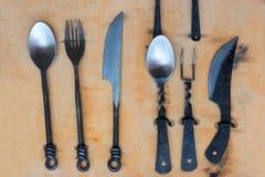 Rustikales handgemachtes Tischbesteck eingestellt auf hölzernes Brett Stockfoto