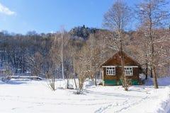 Rustikales Holzhaus in einem Wald des verschneiten Winters auf dem Berg am kalten sonnigen Tag Stockfotografie