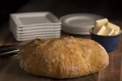 Rustikales italienisches Brot Pugliese mit weißen Platten auf einem hölzernen Schneidebrett mit dem Beschatten Lizenzfreie Stockbilder