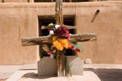 Rustikales Kreuz mit Blumen Stockfotos