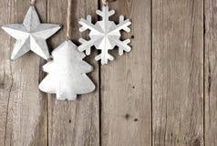 Rustikales Metallweihnachten verziert das Hängen an gealtertem Holz Stockfoto