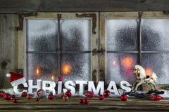 Rustikales Weihnachtsfenster mit roten Kerzen, Pferd und Gruß tex Stockfoto