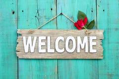 Rustikales Willkommensschild mit der roten Blume, die an beunruhigter antiker grüner Tür hängt Lizenzfreies Stockfoto