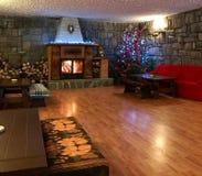 Rustikales Wohnzimmer mit Kamin und Weihnachtsbaum Stockbild