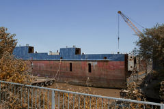 Rusting Barge in Salvage Yard. On river bank Royalty Free Stock Photos