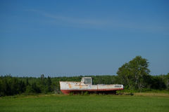 Rusting broken lobster boat in a farm field Royalty Free Stock Photo