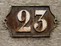 Rusting cast iron number plate. Ornate number 23 die-cast on an old rusting iron house plate on stone pillar Stock Photo