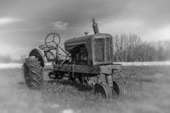 Rusting derelict tractor in rural area. An aging, rusting tractor in a rural field in black and white Stock Image