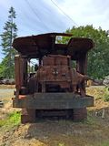 Rusting forestry equipment in green field Stock Image