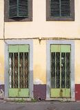 Rusting green metal doors with ornate lattice work on the front of a derelict abandoned shop with faded yellow and red walls and. Shutters in funchal madeira stock photos