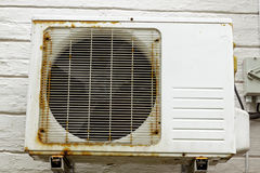 Rusting Metal Exterior Fitted Airconditioning Unit Mounted on W. Old vintage rusting metal exterior fitted airconditioning unit mounted on wall needing Stock Images