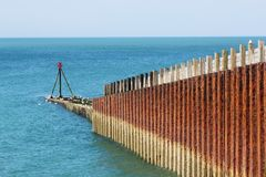 Rusting metal sea defence barrier. Rusting, decaying metal cladding on a wooden sea barrier at Seaford Beach in East Sussex, England Royalty Free Stock Images