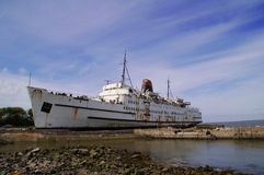 Rusting old passenger ship. Or liner in harbor with blue sky and cloudscape background Royalty Free Stock Photography