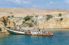 Rusting ship wreck stranded at beach of Angola`s Namib coast. Near Caotinha. Concrete unfinished buildings and desert hills in background Royalty Free Stock Photography
