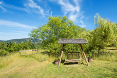 Rusting swing bench in a lush garden.  Stock Photography