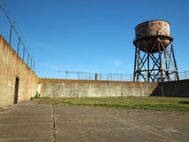 Rusting water tower stands beyond the wall  and bard wire fence Stock Image