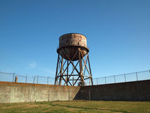 Rusting water tower stands beyond the wall  and bard wire fence Royalty Free Stock Images