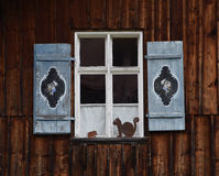 Rustique window in German Alps, with Edelweiss motiv. Brown metal cat and mause decoration Stock Photo