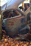 Rusty Abandoned Car. An old wrecked car abandoned along the side of a field Royalty Free Stock Photography