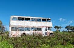 Rusty Abandoned Double-Decker Bus Standing en un campo Fotos de archivo libres de regalías