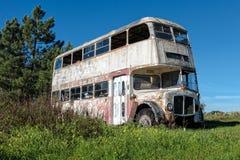 Rusty Abandoned Double-Decker Bus Standing i ett fält Fotografering för Bildbyråer