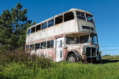Rusty Abandoned Double-Decker Bus Standing in un campo Immagine Stock