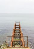 Rusty abandoned pier in sea. Old rusty abandoned pier or bridge in sea Royalty Free Stock Images