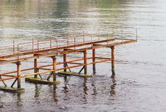 Rusty abandoned pier in sea. Old rusty abandoned pier or bridge in sea Stock Photography