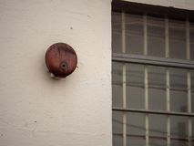 Rusty alarm bell hanging outside of large window outside school building. Rusty alarm bell hanging outside of large window outside a school building royalty free stock photo