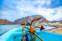 Rusty Anchor on a boat. Old, rusty anchor resting on a fishing boat, blue sky and mountains Stock Photos