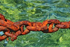 Rusty anchor chain. Over clear water Royalty Free Stock Photo