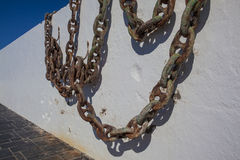 Rusty anchor chains. Old anchor chains hanging from a harbour wall in South Africa Royalty Free Stock Images