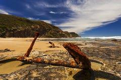 Rusty Anchor en las rocas en la orilla de mar Imagen de archivo
