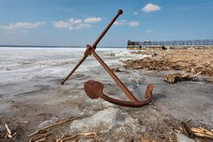 Rusty anchor on the frozen lake coast stock image