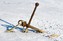 Rusty anchor in ice. Old rusty anchor frozen in ice Royalty Free Stock Photography