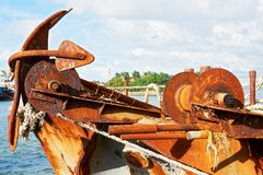 Rusty anchor and other metal parts of an neglected old ship royalty free stock image
