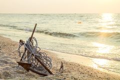 RUSTY ANCHOR WET BEACH SAND AND WHITE SEA WAVE FOAM Stock Photo
