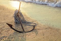 RUSTY ANCHOR WET BEACH SAND AND WHITE SEA WAVE FOAM Royalty Free Stock Photography