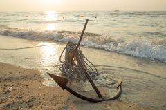 RUSTY ANCHOR WET BEACH SAND AND WHITE SEA WAVE FOAM Stock Photography