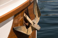 Rusty anchor on a wooden boat Stock Image