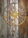 Rusty Antique Cartwheel Nailed à une porte de grange Images stock