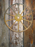 Rusty Antique Cartwheel Nailed to a Barn Door. Stock Images