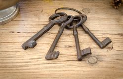 Rusty antique keys on wooden table as background. Royalty Free Stock Photos