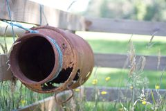 Rusty antique milk can tied to fence Stock Images