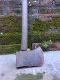 Rusty ax leaning againts the wall stock image