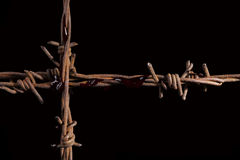 Rusty barb wire cross. Rusty barb wire cross isolated on black background. Religious wars stock photography